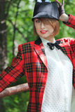 Beautiful young woman in horsewoman suit walks in forest Royalty Free Stock Photo