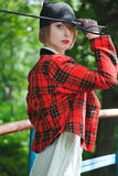 Beautiful young woman in horsewoman suit walks in forest Royalty Free Stock Photos