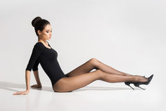 Beautiful, young woman in hosiery sitting on the floor Royalty Free Stock Images