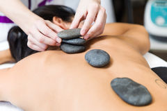 Beautiful young woman with hot stones in beauty spa. Royalty Free Stock Images