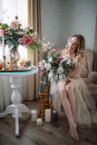 Beautiful young woman in a house dress in the boudoir, decorated with beautiful flowers, sitting on a white bed with a canopy, fas Stock Photography