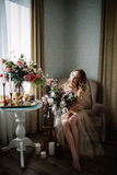Beautiful young woman in a house dress in the boudoir, decorated with beautiful flowers, sitting on a white bed with a canopy, fas. Hion, beauty, sensuality Stock Image