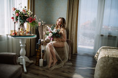 Beautiful young woman in a house dress in the boudoir, decorated with beautiful flowers, sitting on a white bed with a canopy, fas. Hion, beauty, sensuality Royalty Free Stock Photo