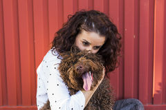 Beautiful young woman hugging her dog, a brown Spanish water dog Stock Photo