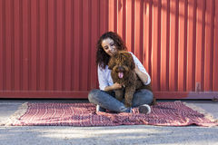 Beautiful young woman hugging her dog, a brown Spanish water dog Stock Photos
