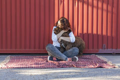 Beautiful young woman hugging her dog, a brown Spanish water dog Royalty Free Stock Image