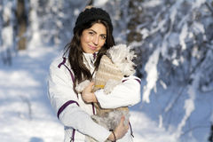 Beautiful young woman  hugging her small white dog in the winter forest .snowing time Royalty Free Stock Photo