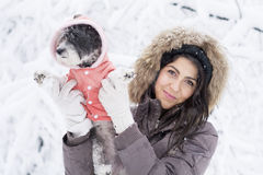 Beautiful young woman  hugging her small white dog in the winter forest .snowing time Royalty Free Stock Photos