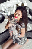Beautiful young woman hugging and holding cat over boker Christm Stock Image