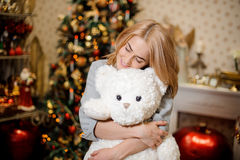 Beautiful young woman hugging a teddy bear, Christmas tree in the background Royalty Free Stock Photos