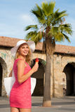 Beautiful young woman with ice cream in a costal city on a hot s Stock Photo