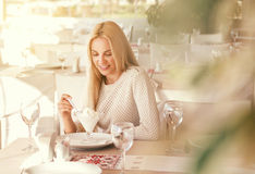 Beautiful young woman with ice cream in sunny cafe Stock Photography