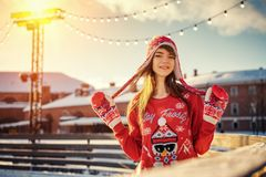 Beautiful young woman on the ice rink, smiling in the sun stock photo