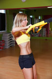 Beautiful young woman illustrating TRX exercise. In the gym Royalty Free Stock Photos