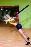 Beautiful young woman illustrating TRX work out. In the gym Stock Photo