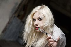 Beautiful young woman in the image of nurse with syringe in hand Stock Photography