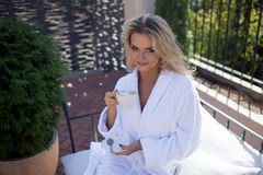 Beautiful Young Woman In Bathrobe Sitting On Terrace And Drink Coffee Royalty Free Stock Images