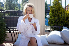 Beautiful Young Woman In Bathrobe Sitting On Terrace And Drink Coffee Stock Images