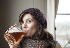 Beautiful Young Woman In Knitted Scarf And Hat Drinks Beer Royalty Free Stock Photography