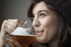 Beautiful Young Woman In Knitted Scarf And Hat Drinks Beer Royalty Free Stock Image
