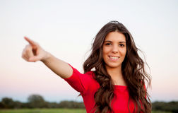 Beautiful young woman indicating something in the countryside Stock Photos