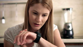 Beautiful young woman indoors sitting in a kitchen sending a voice message via her smart watch.