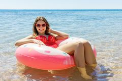 Beautiful young woman with inflatable ring relaxing in blue sea stock photography