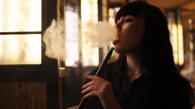 Beautiful young woman inhaling hookah. girl smoking shisha in cafe. Close-up. Warm light. Concept: health, leisure. Beautiful young woman inhaling hookah. Girl stock video