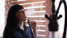 Beautiful young woman inhaling hookah. girl smoking shisha in cafe. Concept: health, leisure. Beautiful young woman inhaling hookah. Girl smoking shisha in cafe stock footage