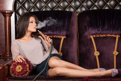 Beautiful young woman inhaling hookah. Royalty Free Stock Photos