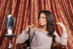 Beautiful young woman inhaling hookah. Stock Photography