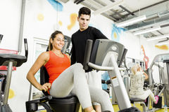 Beautiful young woman instructed by a handsome man in a gym Stock Photo