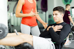 Beautiful young woman instructing a young man in the gym Royalty Free Stock Photos