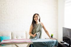 Cute woman ironing some clothes. Beautiful young woman is ironing clothes, looking at camera and smiling Royalty Free Stock Photo