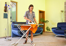 Beautiful young woman ironing his clothes at home. Stock Images