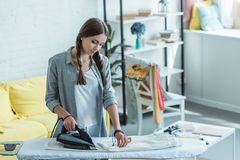 beautiful young woman ironing white pants royalty free stock images