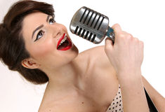 Beautiful young woman isolated on white in studio in old fashion clothes representing pinup and retro style with microphone Stock Images
