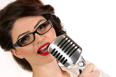 Beautiful young woman isolated on white in studio in old fashion clothes representing pinup and retro style with microphone Stock Photo