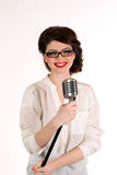 Beautiful young woman isolated on white in studio in old fashion clothes representing pinup and retro style with microphone Royalty Free Stock Photos