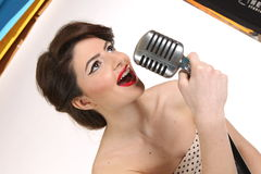 Beautiful young woman isolated on white in studio in old fashion clothes representing pinup and retro style with microphone Royalty Free Stock Photography