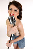 Beautiful young woman isolated on white in studio in old fashion clothes representing pinup and retro style with microphone. Lovely smile Stock Photo