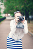 Beautiful young woman in jacket with old retro camera Royalty Free Stock Image