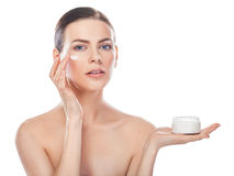 Beautiful young woman with jar of cream and cosmetic cream on a Royalty Free Stock Photography