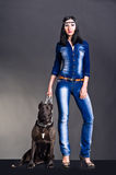 Beautiful young woman in jeans clothes. Standing next to a dog Stock Photos