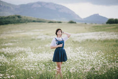 Beautiful young woman in a jeans dress and straw hat posing in a camomile field Stock Photo