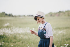 Beautiful young woman in a jeans dress and straw hat posing in a camomile field Royalty Free Stock Photo