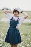 Beautiful young woman in a jeans dress and straw hat posing in a camomile field Royalty Free Stock Photography