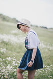 Beautiful young woman in a jeans dress and straw hat posing in a camomile field Stock Image