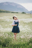 Beautiful young woman in a jeans dress and straw hat posing in a camomile field Royalty Free Stock Images