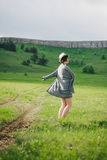 Beautiful young woman in a jeans dress and straw hat posing on a green meadow Royalty Free Stock Photo